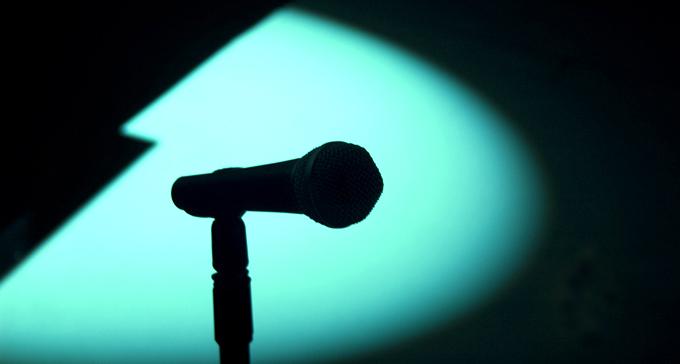 Mikrofon i strålkastarens sken på tom scen. Foto: JF Sebastian/Flickr (CC)