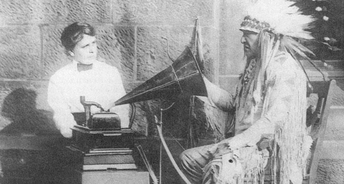 Amerikanska musiketnologen Frances Densmore tolkar sångtexter från en fonografinspelning tillsammans med Mountain Chief, svartfotsindianernas hövding, på Smithsonian Institution 1916.