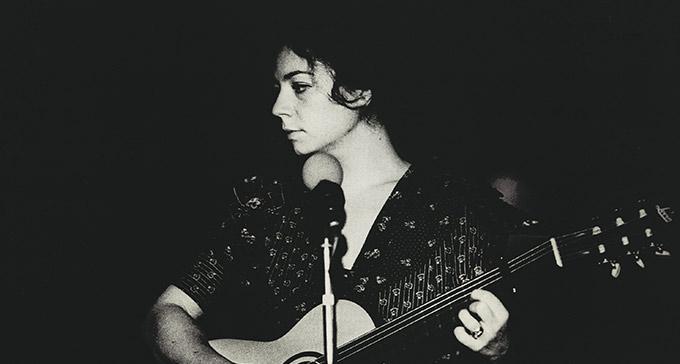 Jelena Jangfeldt spelar gitarr med en mikrofon framför sig.