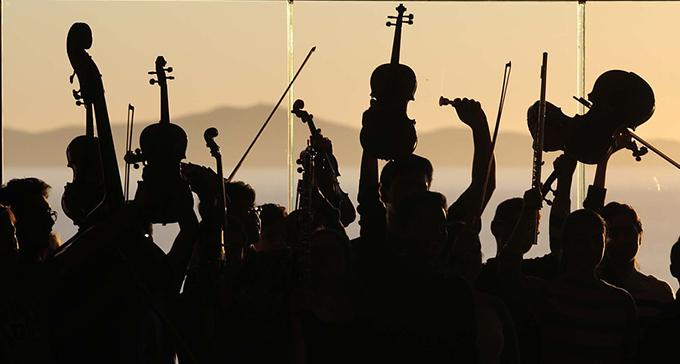Silhuetter av en orkester med sina instrument uppsträckta i luften.