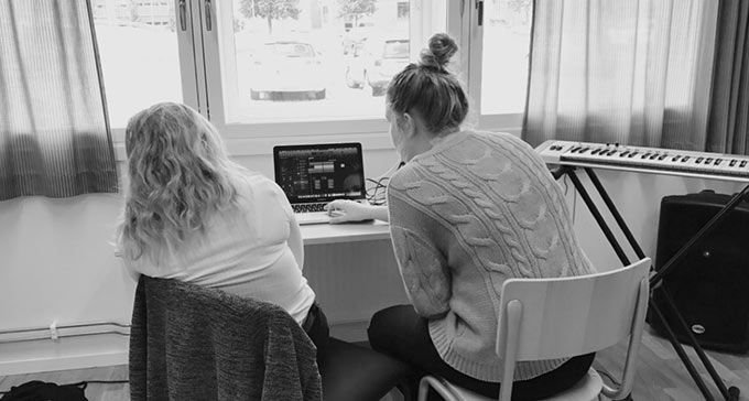 Två kvinnor tittar på en dator.