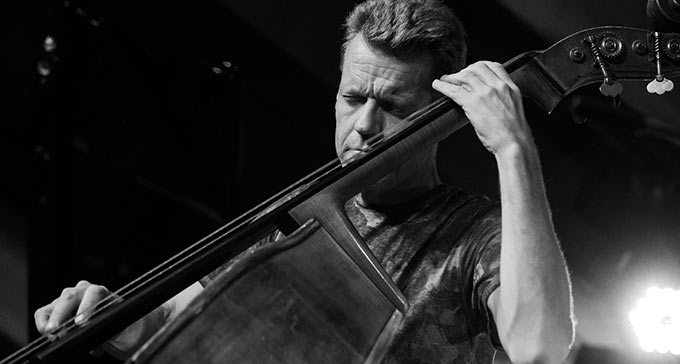 Svartvitt foto av en man som spelar kontrabas.